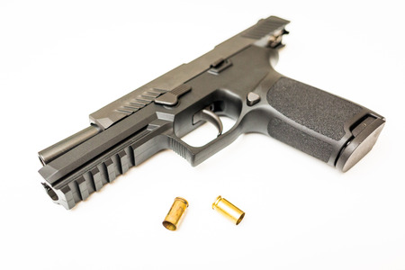 Unloaded handgun with ammo rounds on isolated background Banque d'images