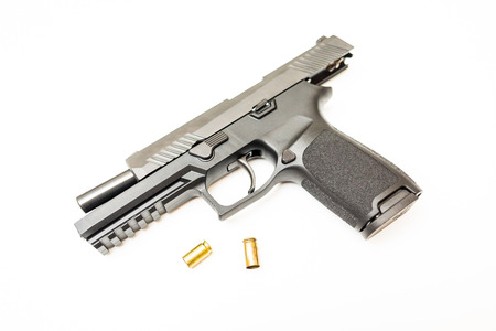 Unloaded handgun with ammo rounds on isolated background Stock Photo