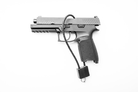 Locked disarmed and secured handgun on isolated white background Stock Photo