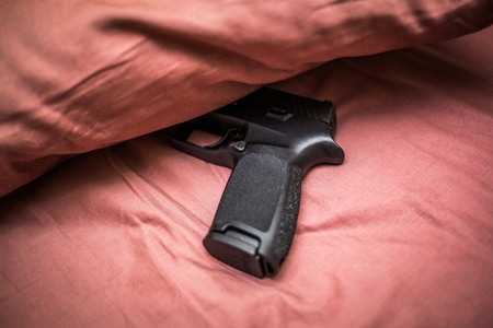 Hidden under bed pillow gun for personal protection Stock Photo