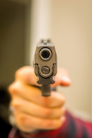 Hand gun pointing indoor home violence with hand
