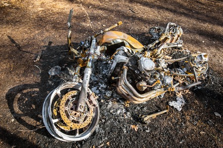 Burned motorcycle after an accident lying down