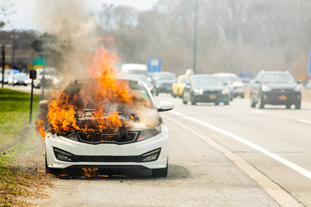 Burning car on fire on a highway road accident at day 版權商用圖片