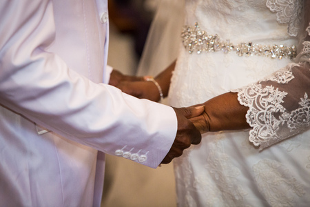 black couple holding hands during marriage ceremony