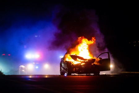 Car on fire at night with police lights in background at night
