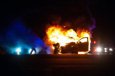 Auto in fiamme di notte con luci della polizia sullo sfondo