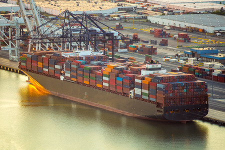 Container ship docked at sea port with cargo at sunset Imagens