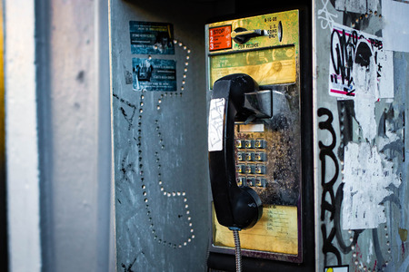 Old retro pay phone box on the street coin