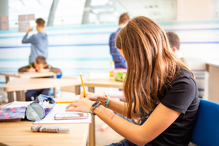 Young girl writing a test in school with other kids Stock Photo