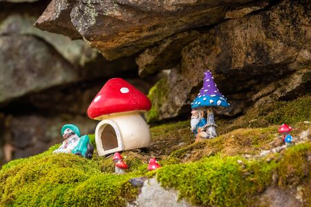 Toy dwarf magical mushroom house hidden in the forest rocks