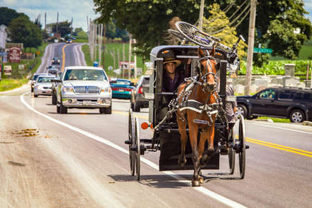Lancaster, PA / USA - 7/4/2013: Amish man riding a retro carriage on the street at day Editöryel