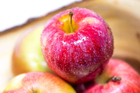 Vivid and fresh couple of red apples in wooden basket on isolated background