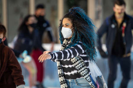 NY, NY, USA - Jan. 22, 2021: Woman skating on ice wearing protective mask during pandemic at day