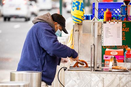 NY, NY, USA - Jan. 22, 2021: Street food seller wearing mask with pretzel at day