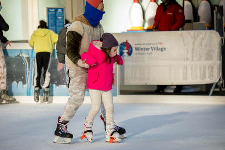 NY, NY, USA - Jan. 22, 2021: Kids learning to skate wearing protective masks on ice rink with parents during pandemic Editoriali