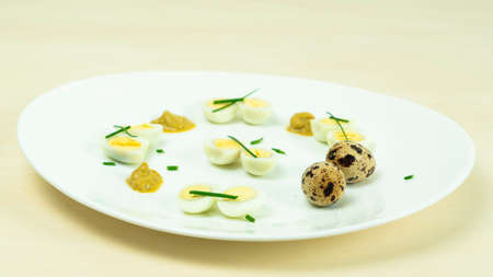 boiled quail eggs with mustard and chives on a plate