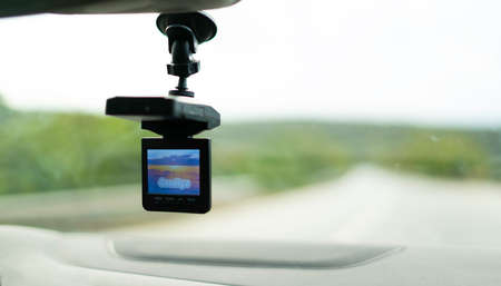 Car video camera (dash cam) inside of car on highway with blurred background of highway road, from perspective of the driver. Concept of safety camera ...