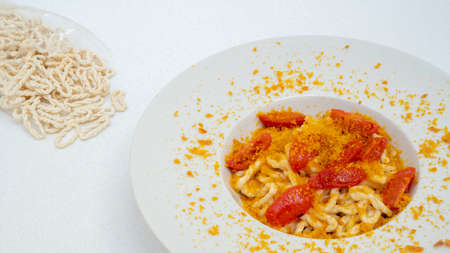 Fresh lorighittas semolina pasta with grated bottarga and cherry tomatoes