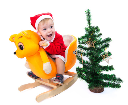 Little boy in Santa Claus suit riding a toy cat photo