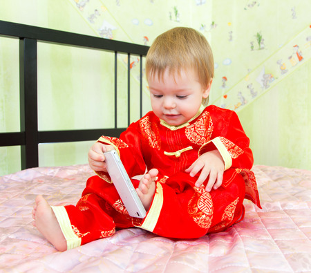Funny toddler trying to input phone number by his foot
