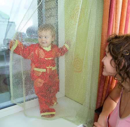 Baby boy is hiding from mother behind the curtain