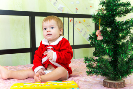 nappy new year: Funny boy sits near new year fir and squeezes his treasures Stock Photo