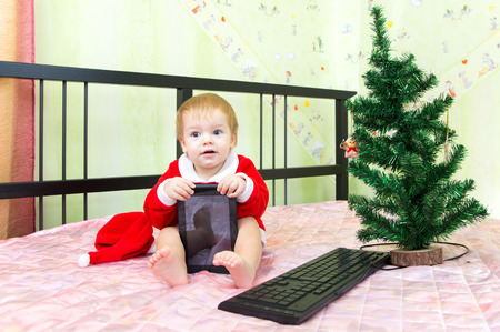 Pleased baby in new year suit with tablet computer photo