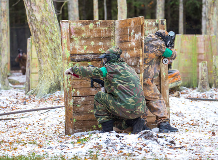 fortification: Two paintball shooters defending the fortification on snow Stock Photo