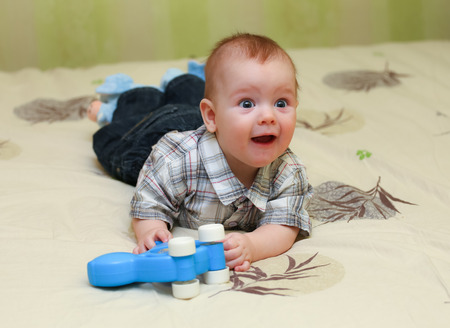 pleased: Funny pleased little boy lying on the bed with his toy