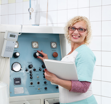 tuning: Smiling female specialist tuning medical equipment in laboratory Stock Photo