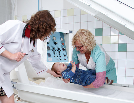 put pressure: Female doctor and nurse put little boy in pressure chamber Stock Photo