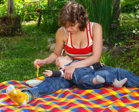 feeds: Mother feeds child on bright plaid outdoors Stock Photo