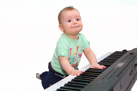 Small funny boy playing electric piano photo