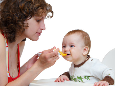 Mother spoon-feed her obedient baby photo