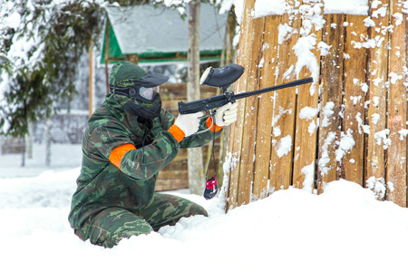 fortification: Paintball player sitting on snow near wooden fortification and shooting