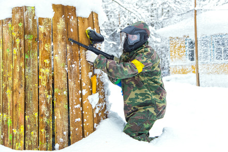 bank activities: Beautiful girl with air gun playing paintball in winter Stock Photo