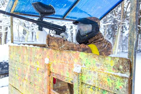 hombre disparando: Tiroteo hombre de la pistola de paintball detr�s de fortificaci�n de madera Foto de archivo