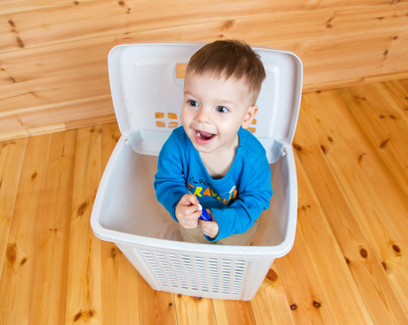 one year old: Smiling one year old boy getting out from garbage can