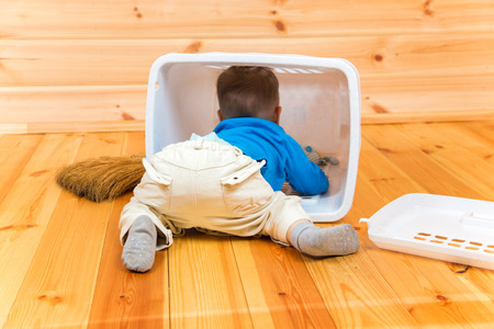 overturn: Little active boy helps to clean the house getting inside bin