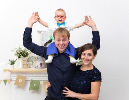 Young happy family with one year old boy on father shoulders photo