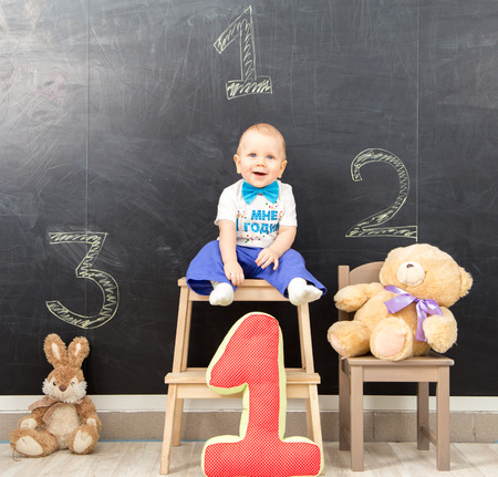 podium: Happy one year old boy takes first place on the podium