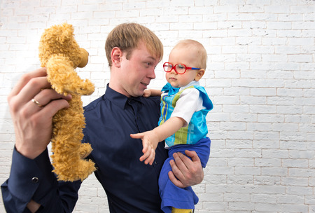 one year old: Young dad shows teddy bear to his one year old son on brick background Stock Photo