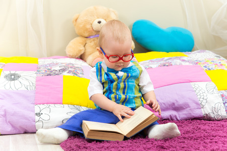funny glasses: Funny one year old boy reading a book in glasses