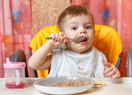 Little boy eats buckwheat cereal by himself