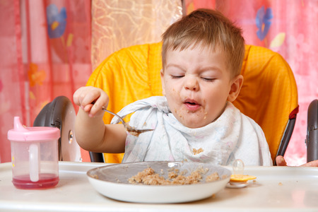 grimace: Funny baby with grimace holds spoon with buckwheat cereal Stock Photo