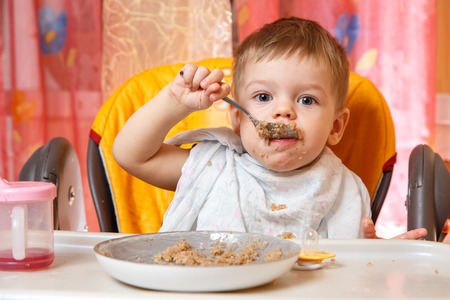 independently: Handsome boy eats buckwheat cereal independently Stock Photo