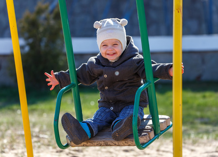 fearless: Fearless kid swinging on the swing taking hands free Stock Photo