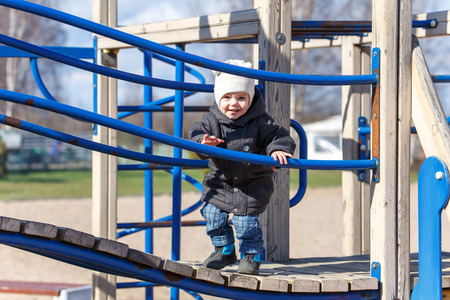 on playground: Little child walks along the boards on the playground