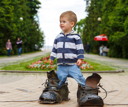 ni�o de pie: Desconcertado dos a�os del muchacho de pie con botas gigantes