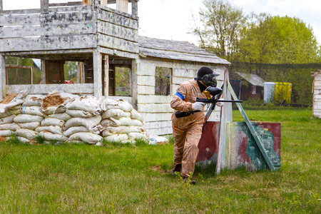paint gun: Paintball warrior with paint gun and fortress behind Stock Photo